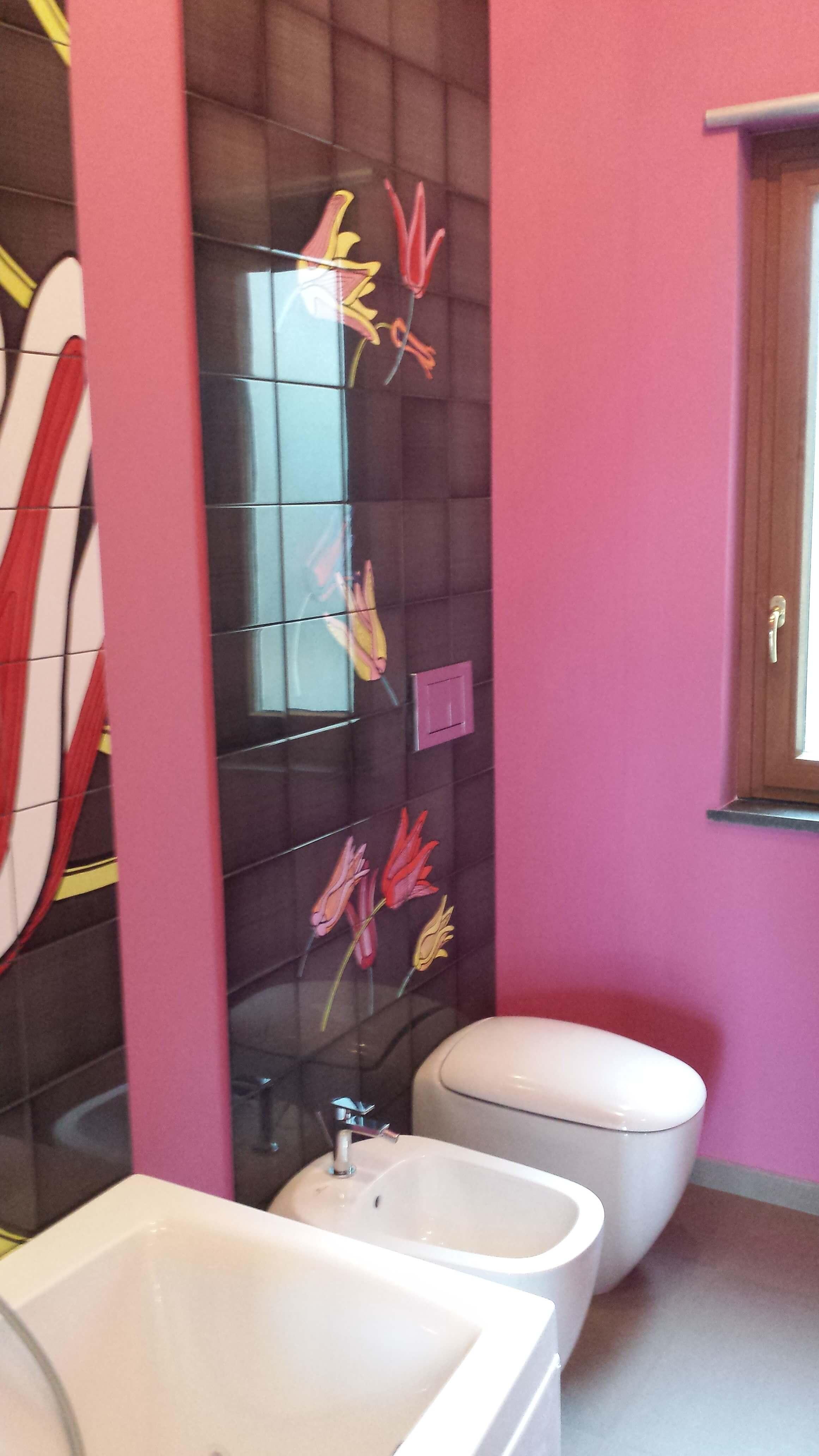 bagno con muri rosa, piastrelle nere con fiori rosa e sanitari bianchi