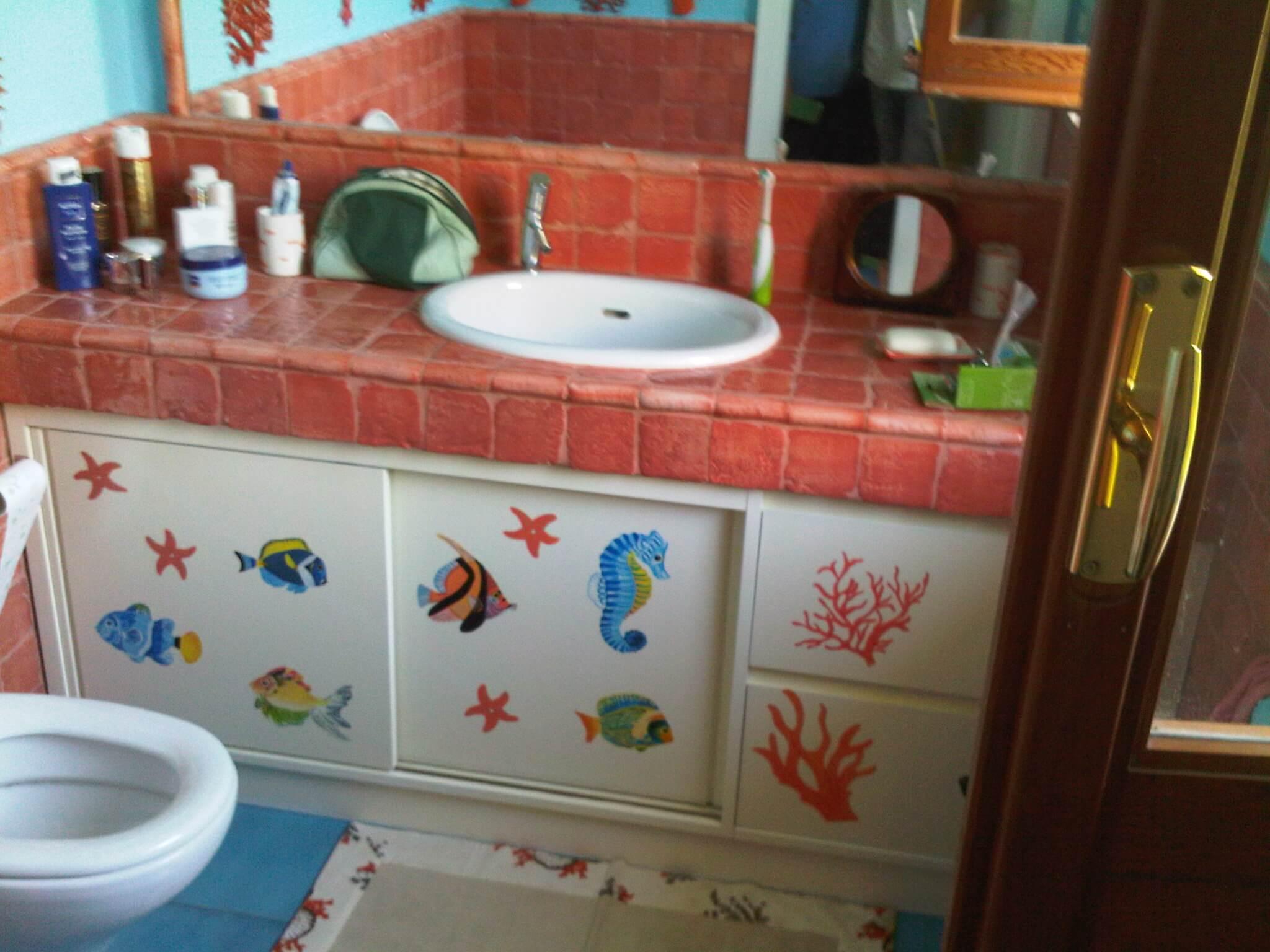 bagno con mobile bianco con decorazioni marine e piano in mattonelle rosse