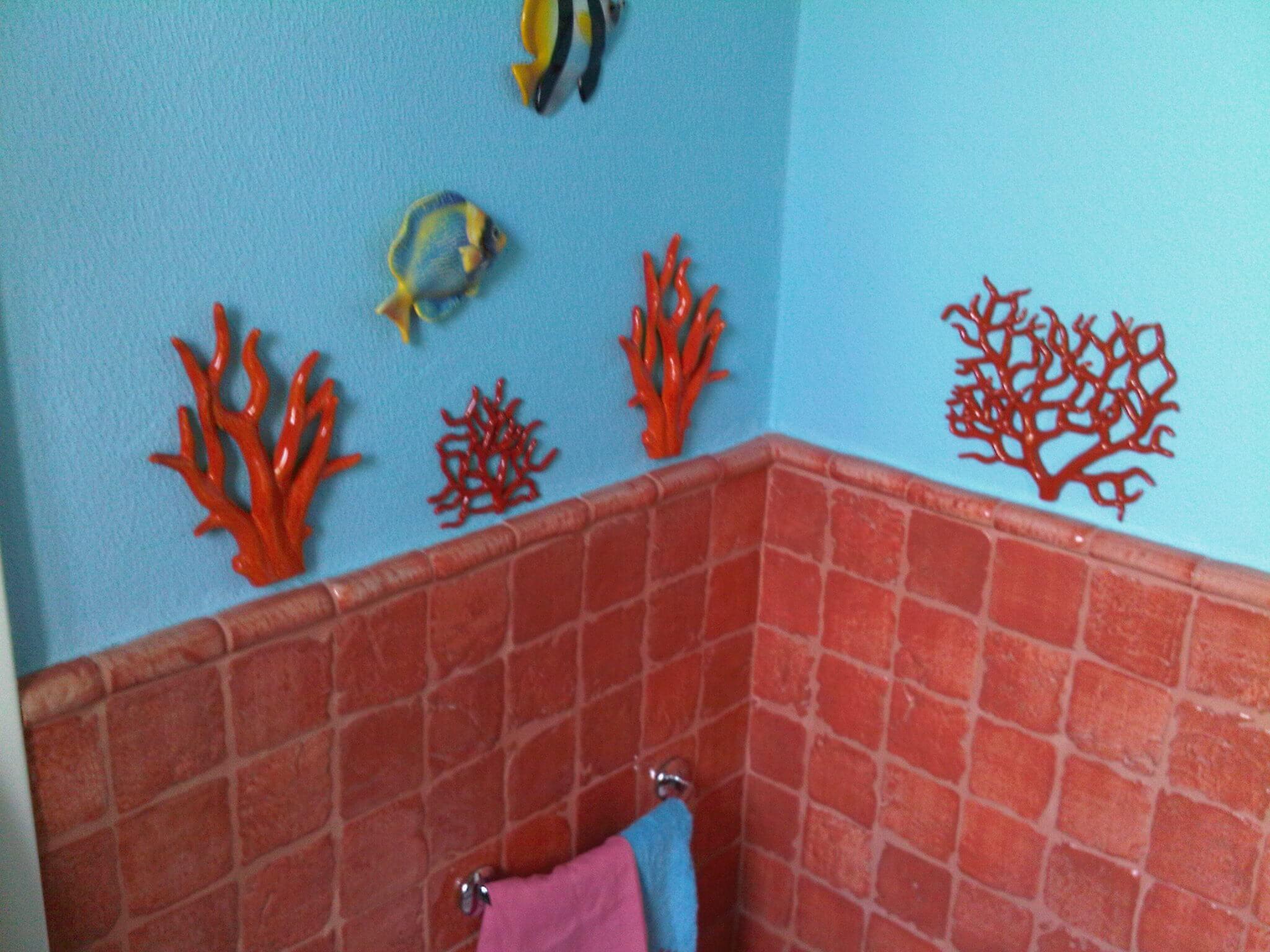 muro azzurro con piastrelle rosso mattone e decorazioni marine