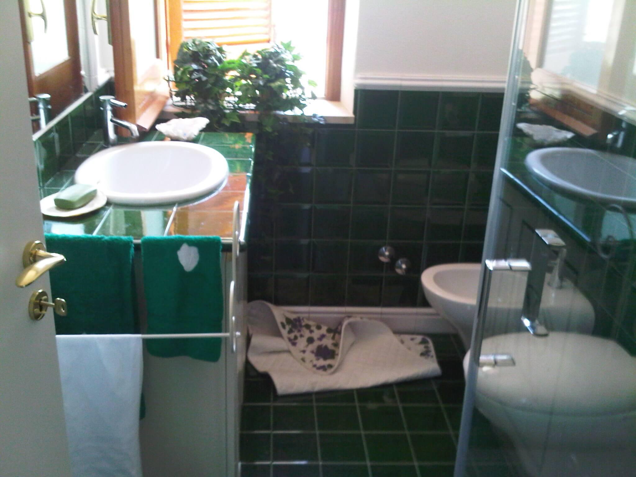 bagno con mattone verdi, sanitari e mobile bianco
