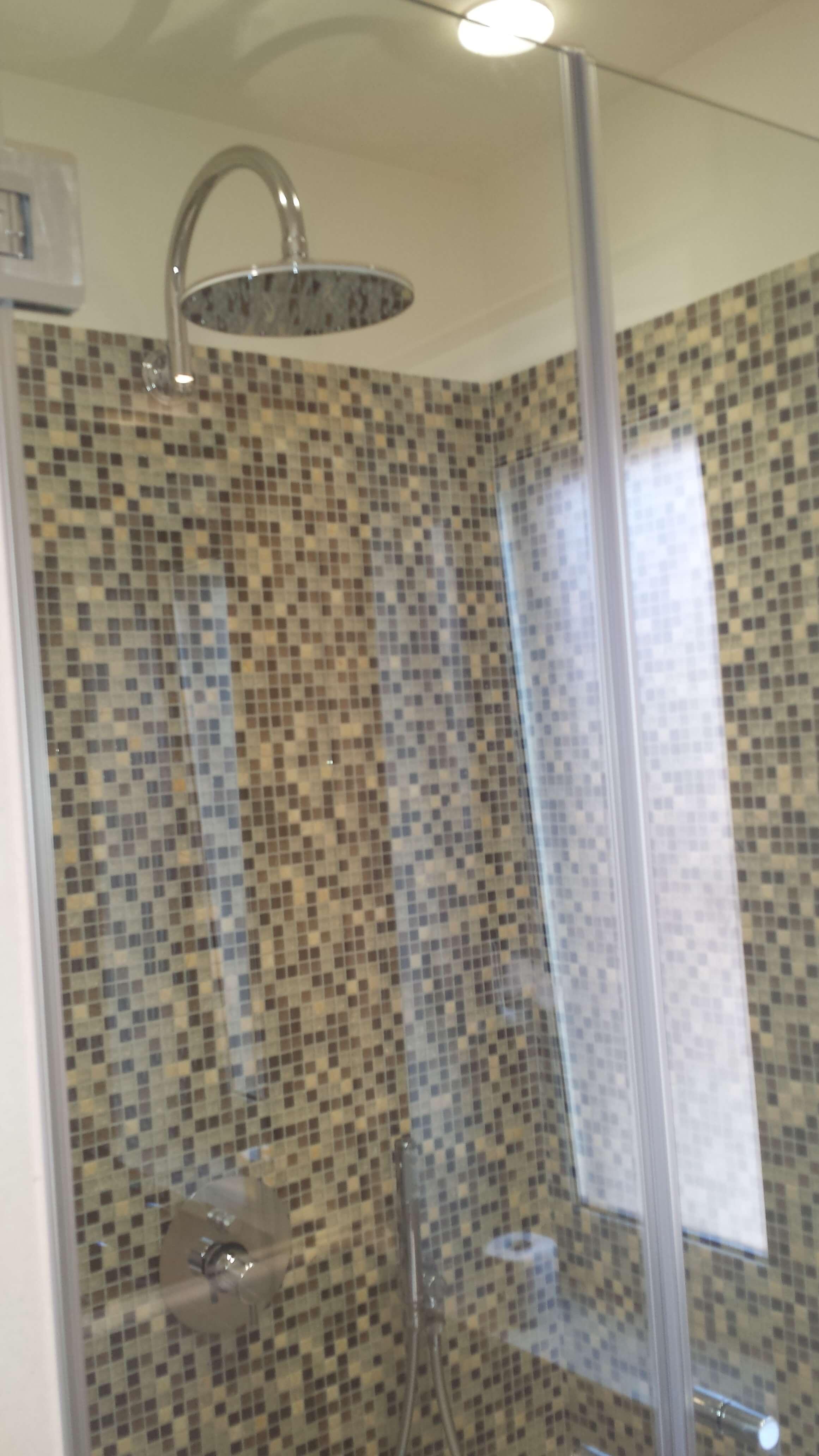 doccia con soffione fisso dall'alto e pareti a mosaico