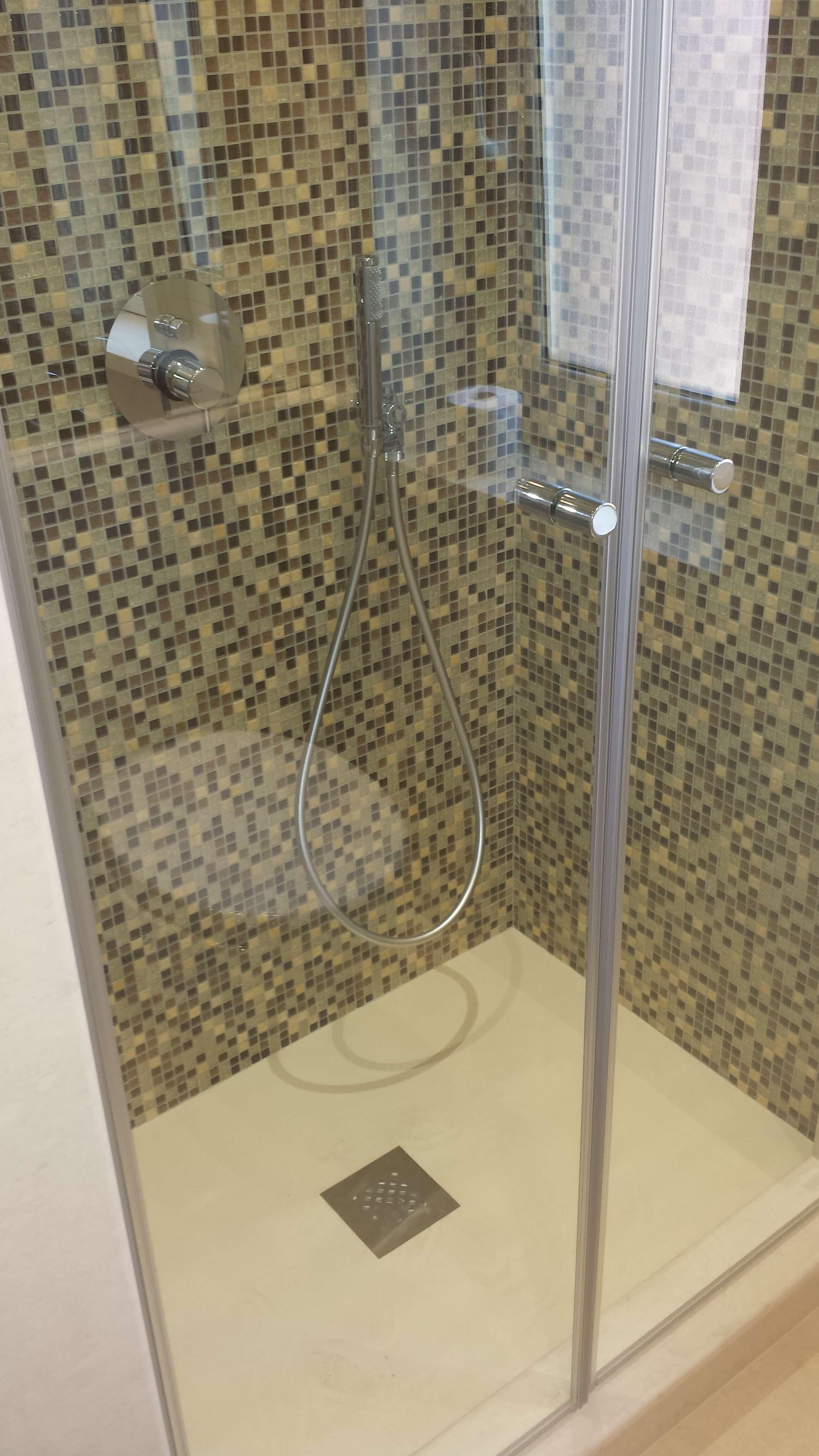 doccia con porta a vetri e pareti a mosaico