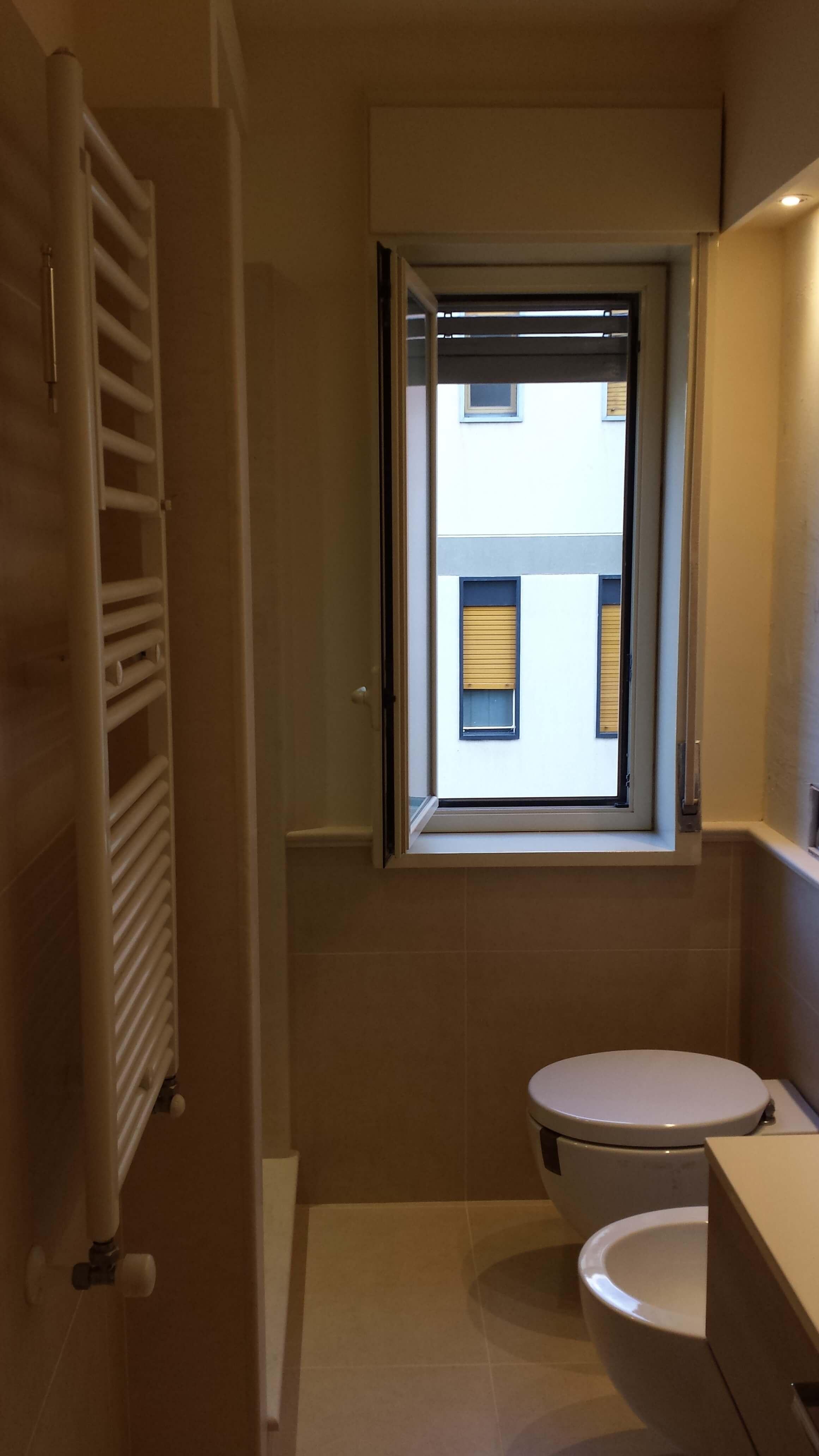 bagno con pareti chiare, scaldasalviette e sanitari