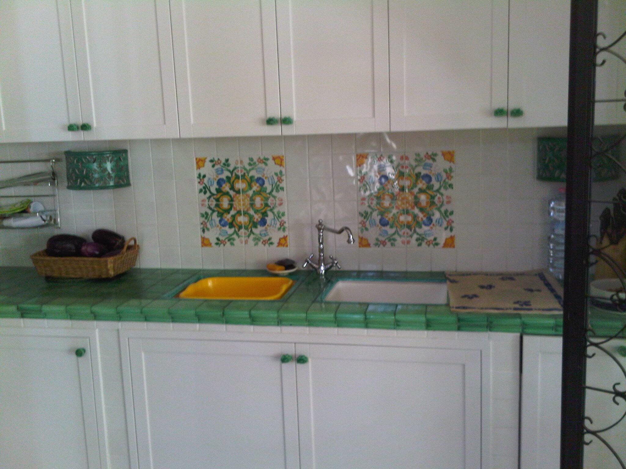 cucina con mobili bianchi, piano verde e piastrelle a tema sul muro