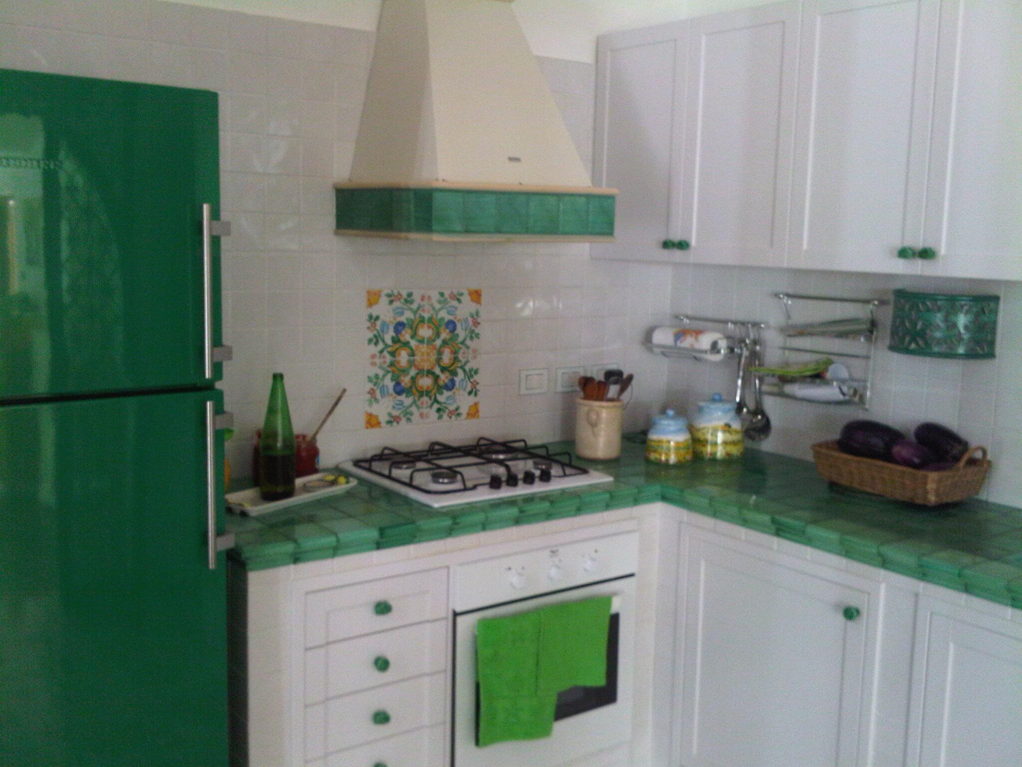 cucina con mobili bianchi, piano in mattonelle verdi e frigo verde