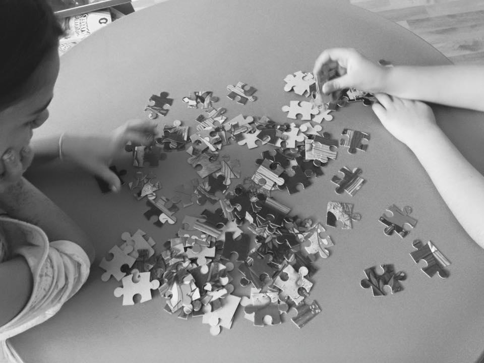 una bambina e una mano davanti a dei pezzi di puzzle