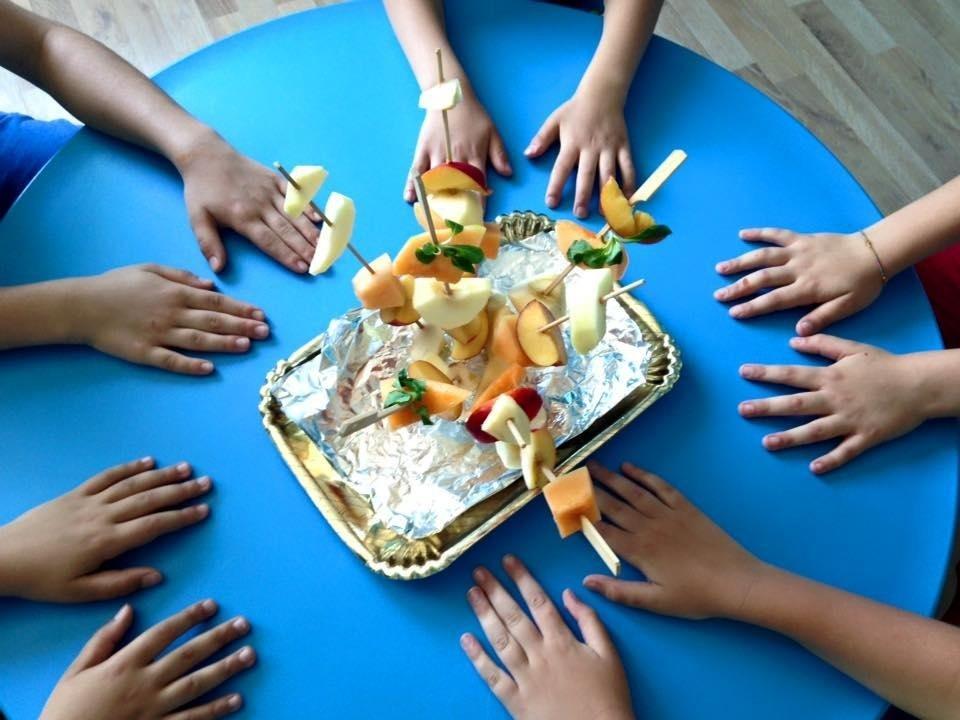 delle mani appoggiate su un tavolo e al centro una torta