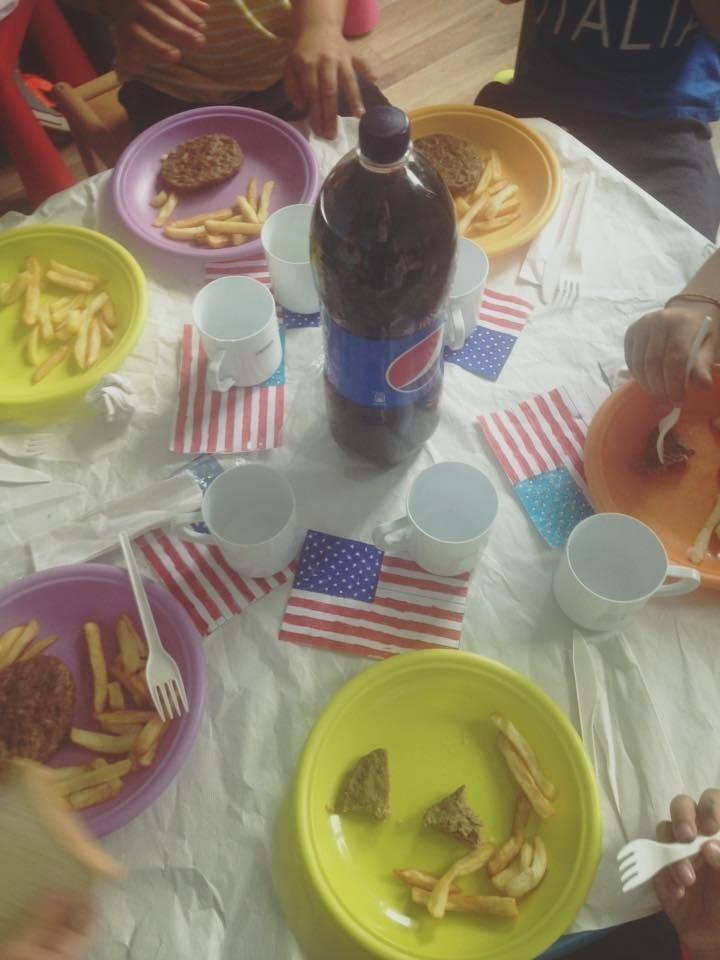 dei piatti colorati con patatine, hamburger e una bottiglia di Pepsi