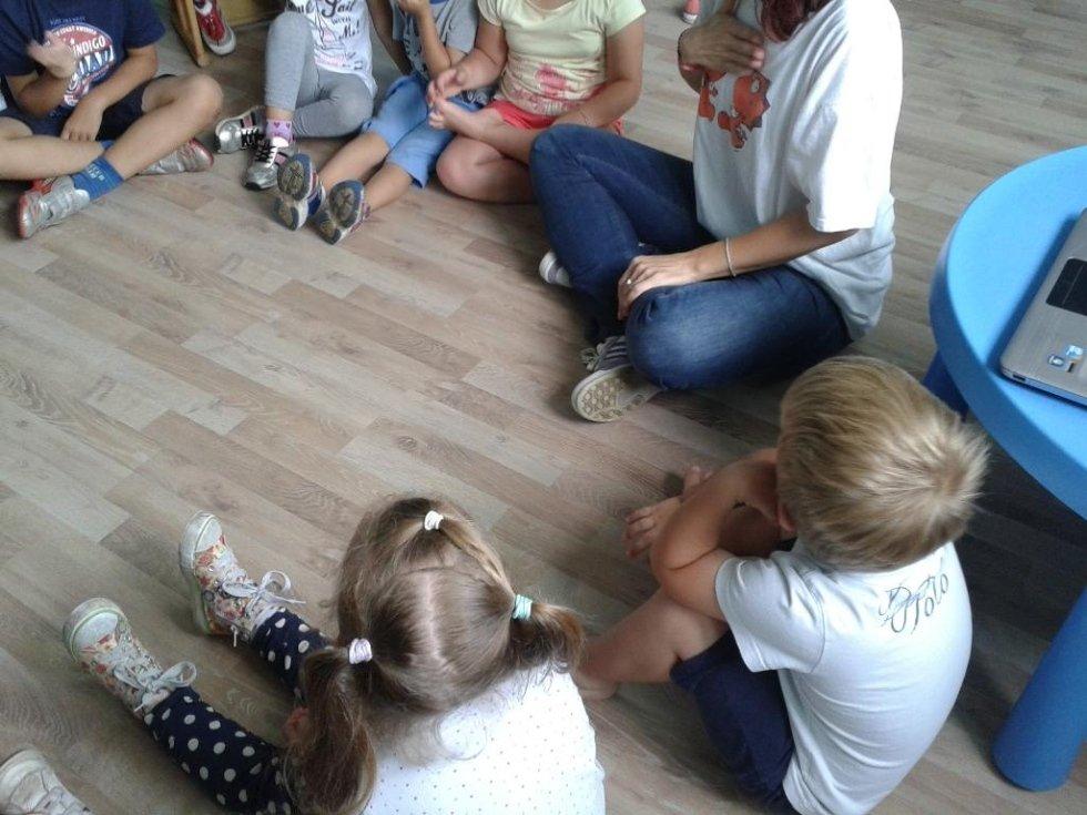 dei bambini seduti in cerchio