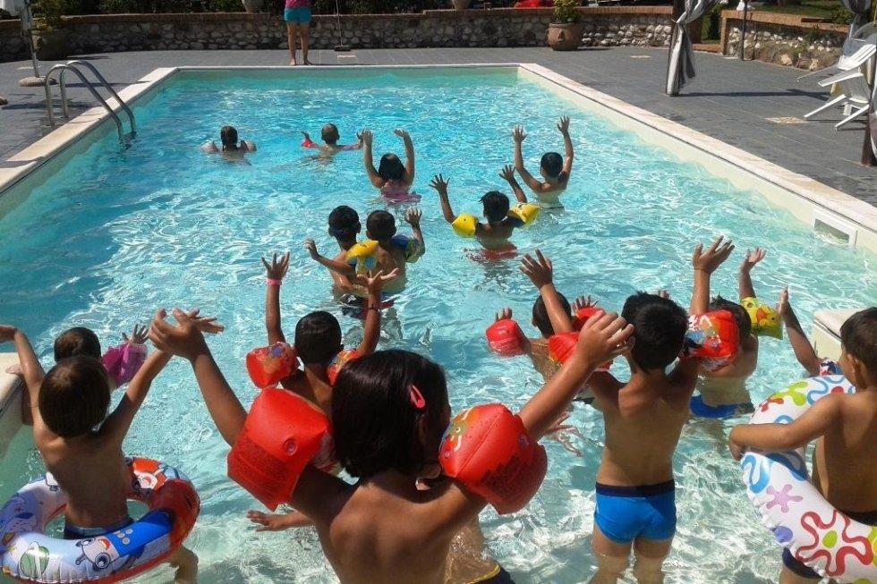 dei bambini con dei braccioli in una piscina