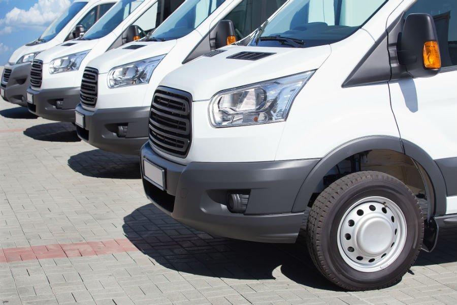 trei furgoni bianchi parcheggiati uno di fianco all'altro
