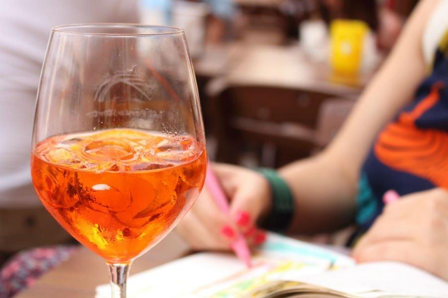 Primo piano di un bicchiere con un cocktail arancione e del ghiaccio