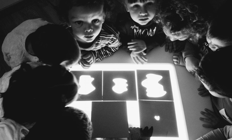 bambini attorno a lavagna luminosa