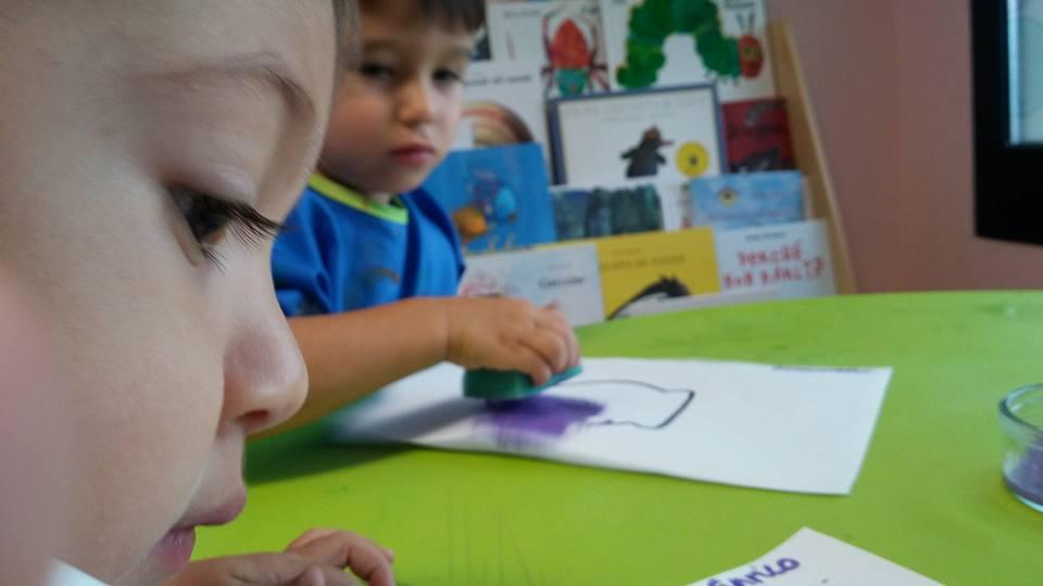 primo piano di un bambino e bambino che pittura in secondo piano