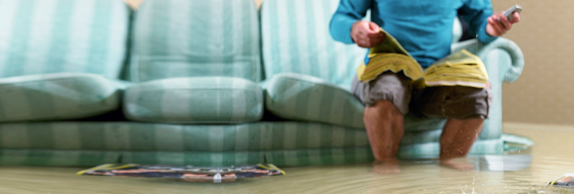 man in flooded living room looking through the yellow pages