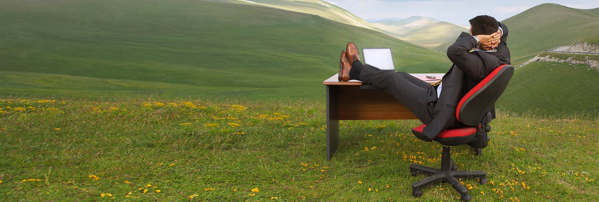 Business man sitting at a desk in a field overlooking mountains looking relaxed