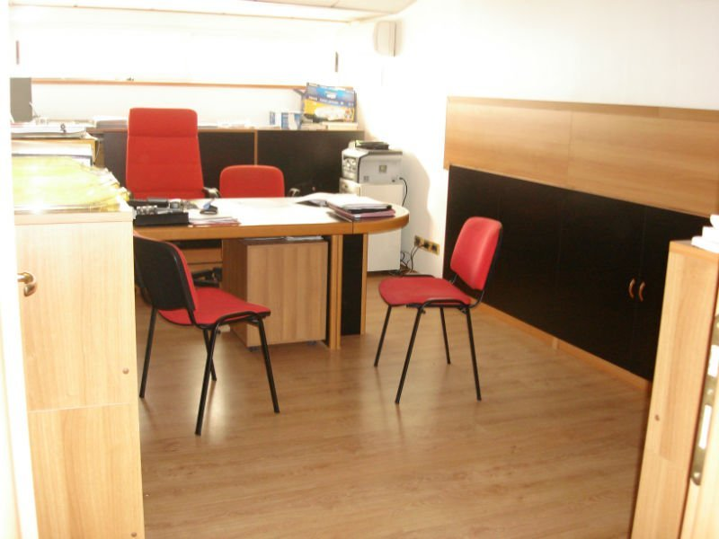 un ufficio con una scrivania e tre sedie rosse