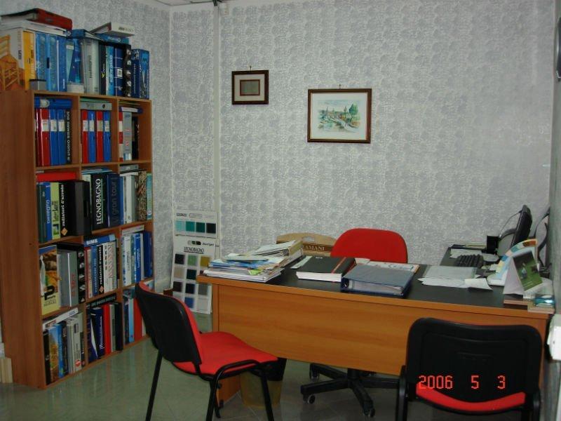 un ufficio con una scrivania e parete con una tappezzeria di color grigio