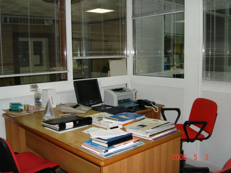 un ufficio con una scrivania e delle vetrate attorno
