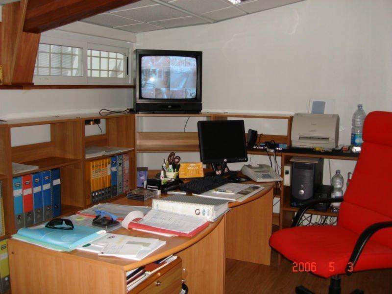 un ufficio con una scrivania lunga, un mobile con dei raccoglitori e una Tv al angolo