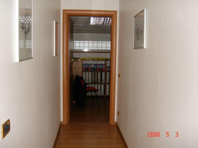 un corridoio con pavimento in parquet e in fondo la porta di un ufficio