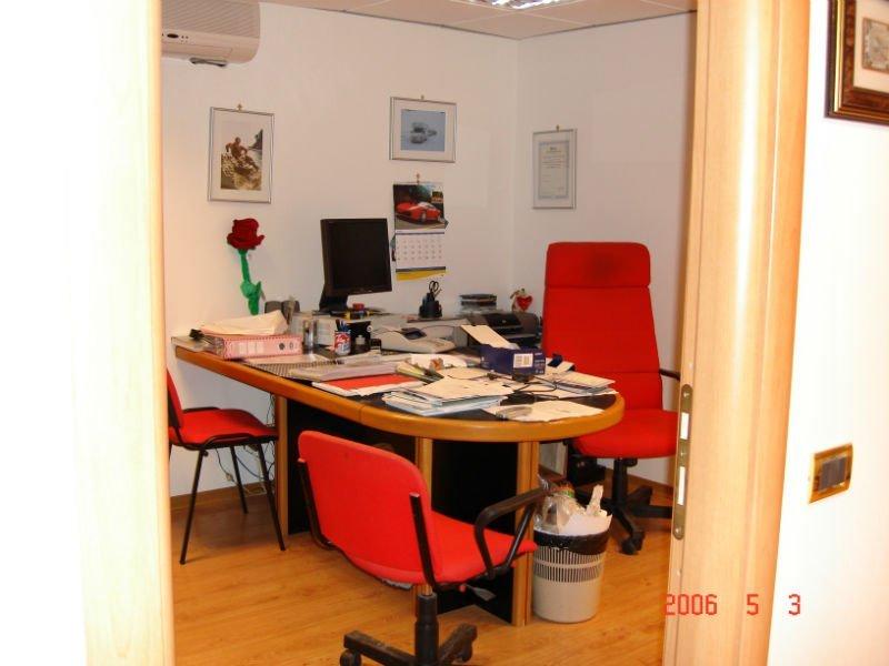 una scrivania di legno di color legno e nero e tre sedie di color rosso