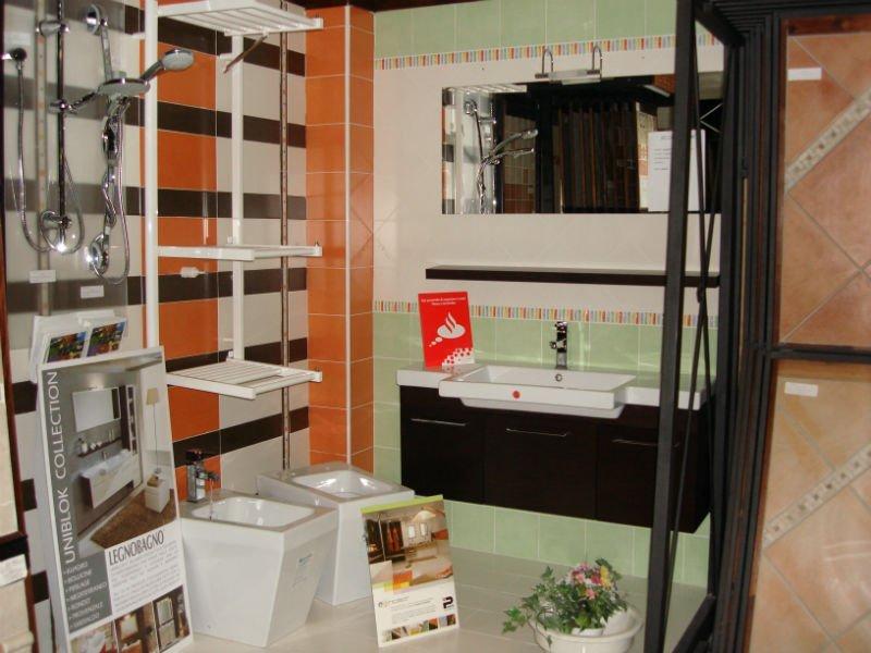 un lavabo con sotto un mobile di legno scuro e accanto dei sanitari moderni
