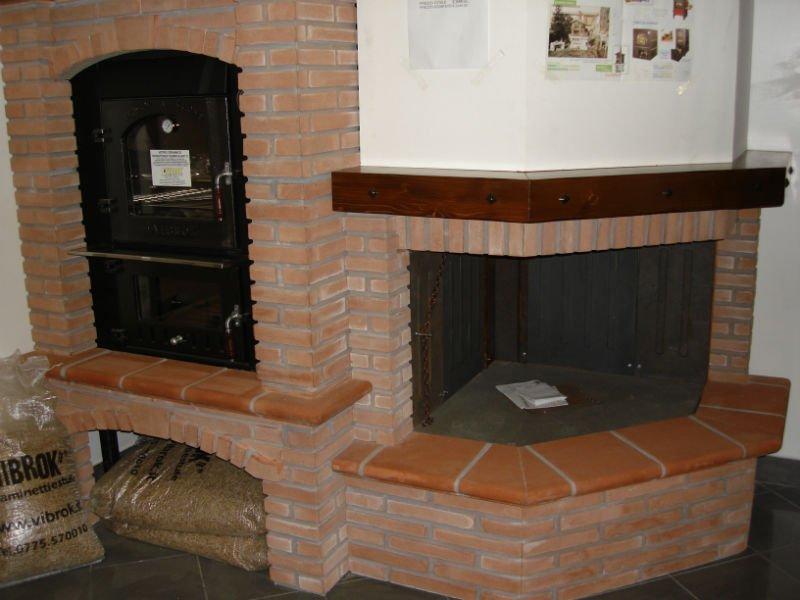 un camino a legna e accanto due forni con un muro in mattoni