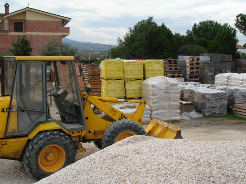 un escavatore e accanto dei bancali con del materiale imballato