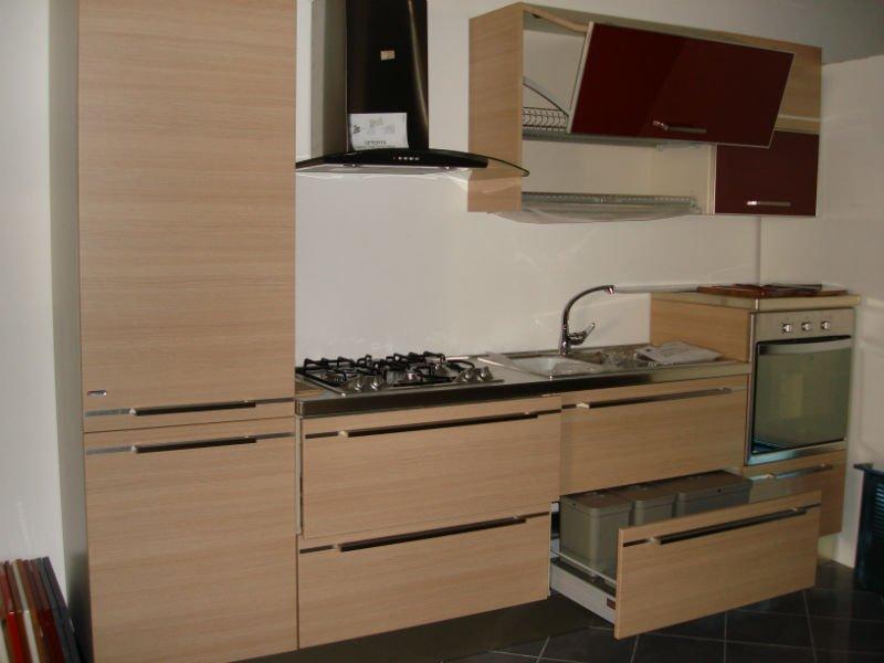 una cucina a blocco  in legno chiaro e bordeaux