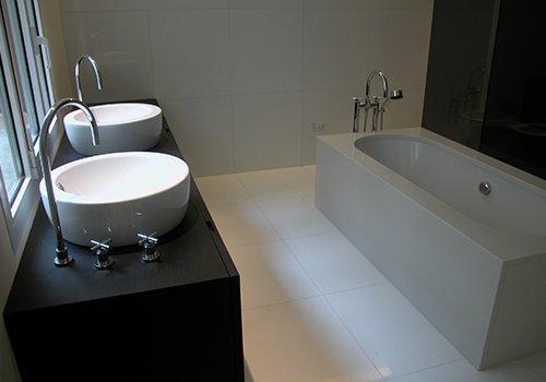 un bagno con una vasca e un mobile di color bianco con due lavabi rotondi