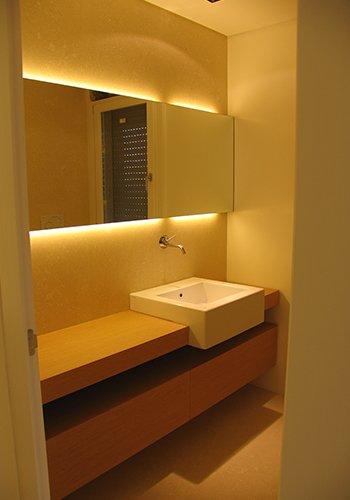 un bagno con un lavabo quadrato e uno specchio a muro