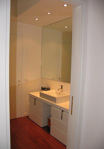un bagno con un lavabo rettangolare e uno specchio a muro