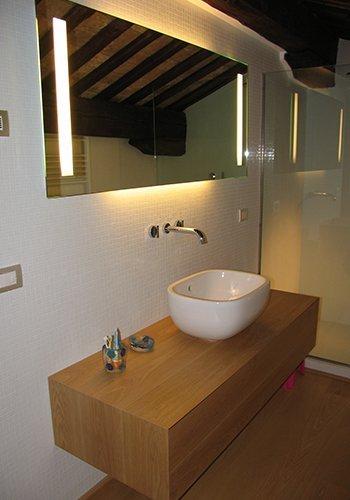 una mensola in legno con sopra un lavabo moderno