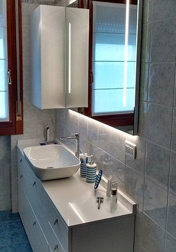 un bagno con un mobile di color bianco, un lavabo rettangolare