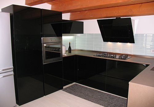 una cucina con i mobili di color nero e una cappa moderna