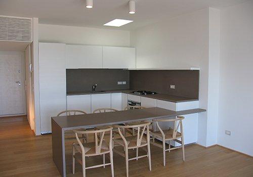 una cucina ad angolo di color bianco e delle sedie in legno