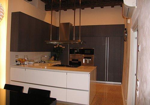 un cucina ad angolo con i mobili di color grigio e bianco