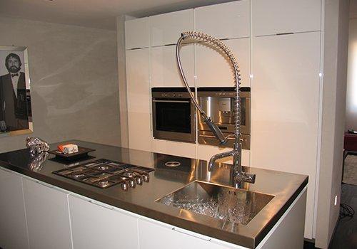 una cucina con i mobili di color bianco e un top in acciaio