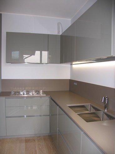 una cucina con dei mobili di color panna e un lampadario