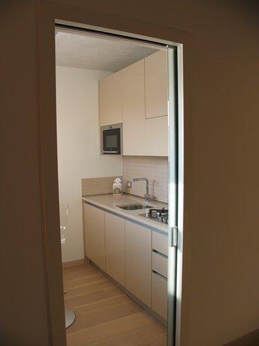 una cucina con  mobili di color bianco