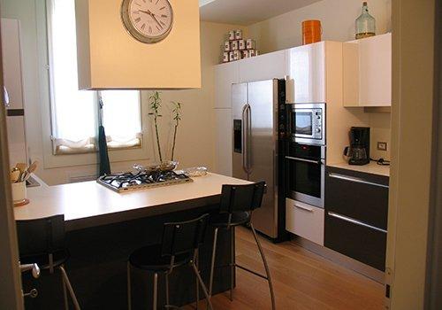 una cucina con un mobile di color bianco e grigio, una penisola con dei fornelli e degli sgabelli