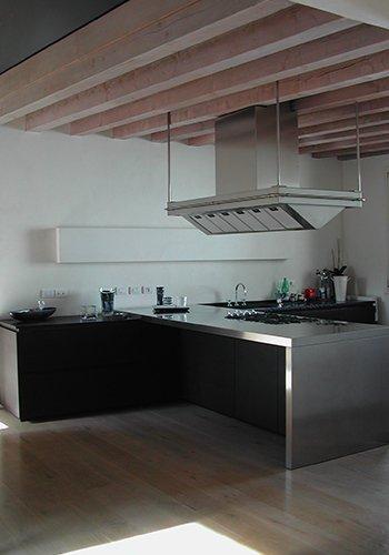 una cucina angolare con i mobili di color nero e un top in acciaio