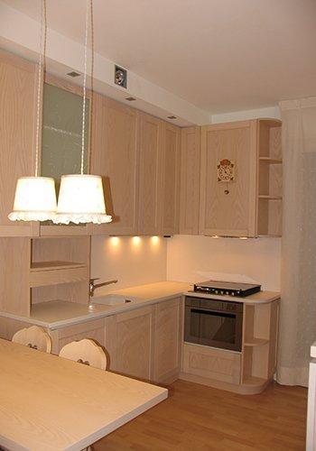 un cucina angolare in legno chiaro e due lampade a sospensione