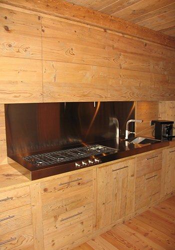 una cucina in legno, dei fornelli e  un lavandino in acciaio inox