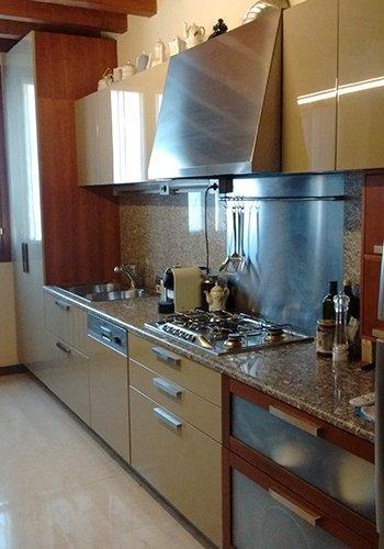 una cucina con le ante laccate e un top in marmo arlecchino
