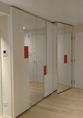 degli armadi di color bianco con delle ante con uno specchio