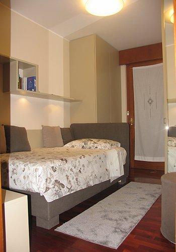 una sala con un divano letto di color grigio e un pavimento in legno
