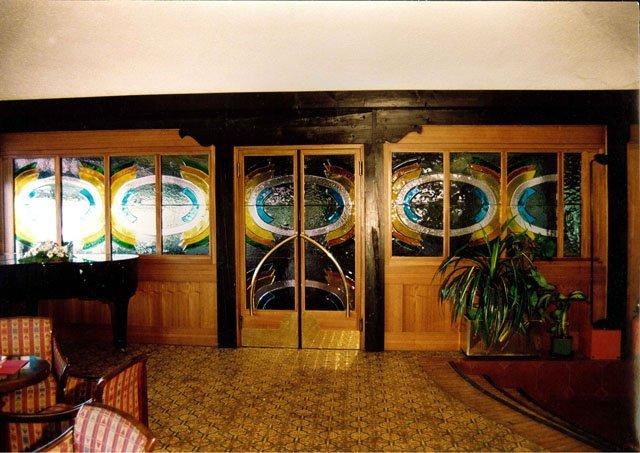 un corridoio con un mobile di color avorio e pavimento in legno