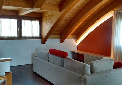una sala con un divano ad angolo e un tetto in legno